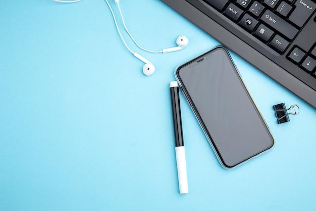 Bovenaanzicht van kantoorconcept met hoofdtelefoon voor mobiele telefoons op blauwe ondergrond