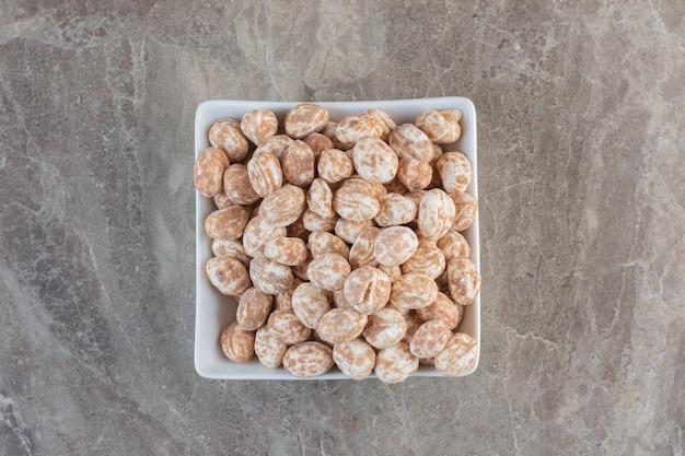 Bovenaanzicht van karamel snoepjes in witte kom over grijs oppervlak.