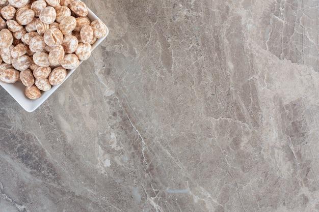 Bovenaanzicht van karamel snoepjes over grijze achtergrond.