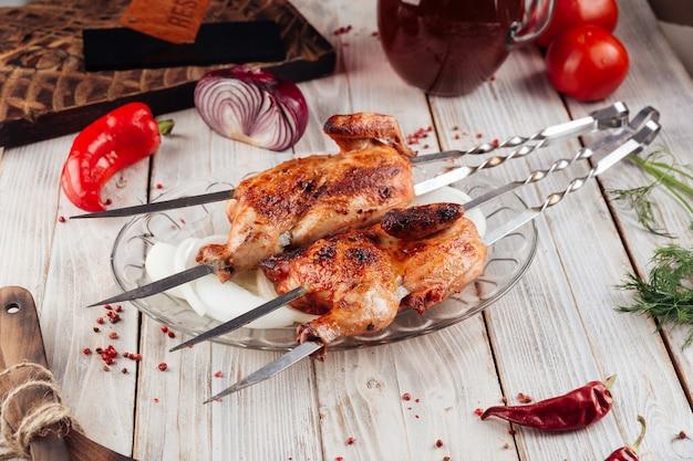 Bovenaanzicht van kaukasische gegrilde kipspiesjes op de lichte houten tafel met sauzen
