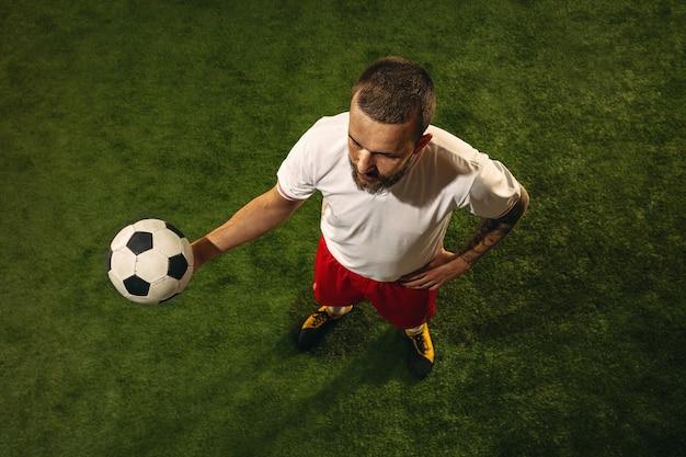 Bovenaanzicht van kaukasische voetbal of voetballer op gras. jonge mannelijke sportieve model training, oefenen. bal trappen, aanvallen, vangen. concept van sport, competitie, winnen.