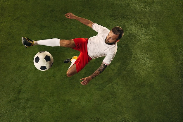 Bovenaanzicht van kaukasische voetbal of voetballer op groene achtergrond van gras. jonge mannelijke sportieve model opleiding, oefenen. bal trappen, aanvallen, vangen. concept van sport, competitie, winnen.