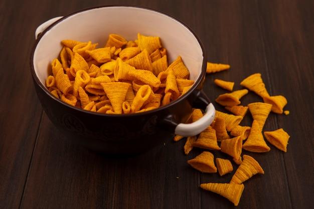 Bovenaanzicht van kegelvorm gebakken maïs snacks op een kom op een houten tafel