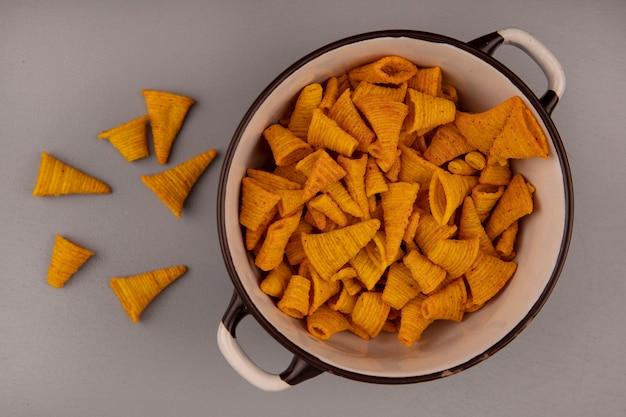 Bovenaanzicht van kegelvorm gebakken maïs snacks op een kom