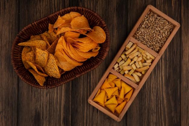 Bovenaanzicht van kegelvormige bugels chips op een houten onderverdeelde plaat met gepelde zonnebloempitten met pittige chips op een emmer op een houten muur
