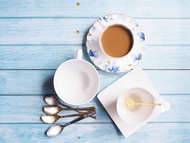 Bovenaanzicht van keramische koffiekopje theekop en schotel met drank warme koffie drinken in mok en lepel op tafel.