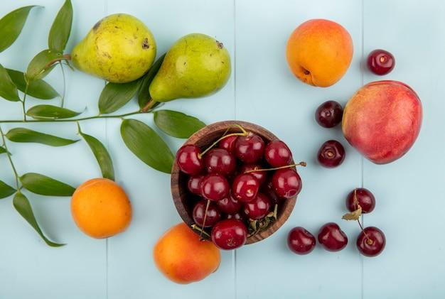 Bovenaanzicht van kersen in kom en patroon van peren abrikozen perzik kersen met bladeren op blauwe achtergrond