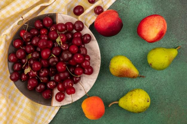 Bovenaanzicht van kersen in plaat op geruite doek en patroon van perziken, peren, kersen en abrikoos op groene achtergrond