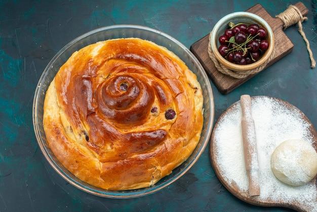 Bovenaanzicht van kersentaart met deegmeel en verse zure kersen op donkerblauw, taartcake zoet fruit