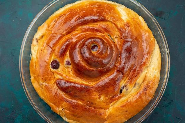 Bovenaanzicht van kersentaart met gebakken kersen binnen op een donker bureau, taartcake fruitkers