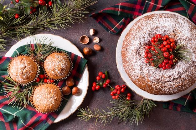 Bovenaanzicht van kerst cupcakes en cake met rode bessen