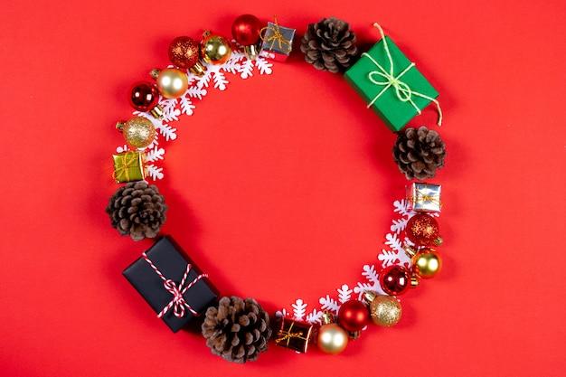 Bovenaanzicht van kerst geschenkdozen met dennenappels, rode bessen op rode papier achtergrond.