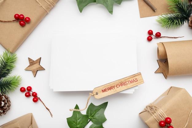 Bovenaanzicht van kerst samenstelling met geschenkdoos, lint, fir takken, kegels, anijs op witte tafel