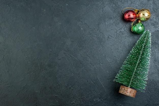 Bovenaanzicht van kerstboom en decoratieaccessoires aan de linkerkant op zwarte achtergrond