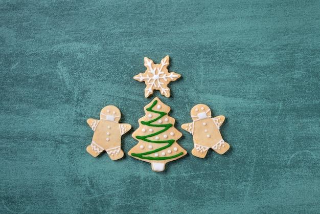 Bovenaanzicht van kerstboom en sneeuwvlok cooikes met speculaaspop met masker op groene tafel achtergrond.