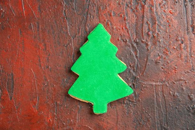 Bovenaanzicht van kerstboomkoekje op donkerrood oppervlak