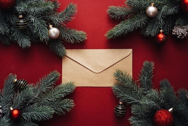 Bovenaanzicht van kerstboomtakken met ornamenten en envelop