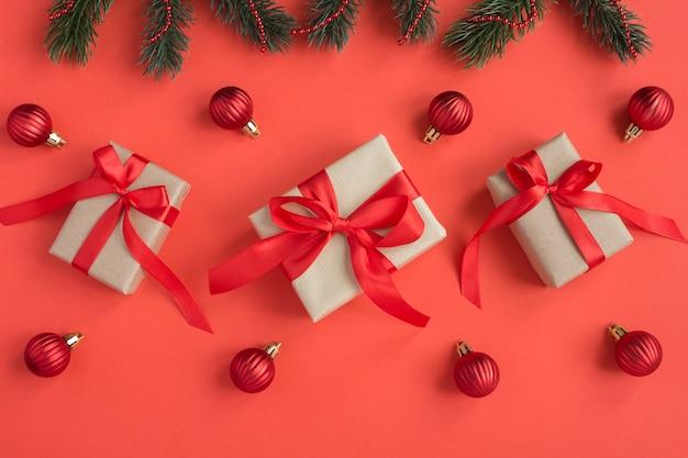 Bovenaanzicht van kerstcadeaus met tiew rode strik en kraal op de rode achtergrond. ruimte kopiëren.