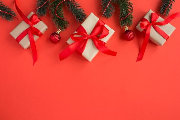 Bovenaanzicht van kerstcadeaus met tiew rode strik op de rode achtergrond. ruimte kopiëren. Premium Foto