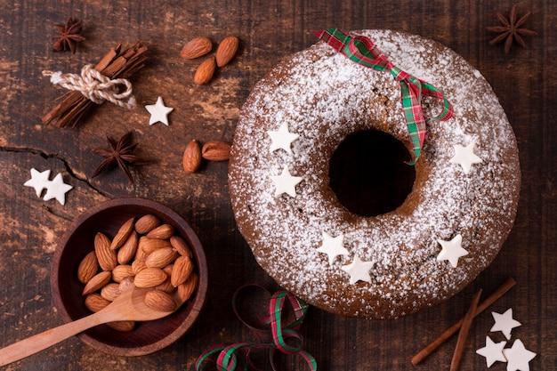 Bovenaanzicht van kerstcake met amandelen en kaneelstokjes