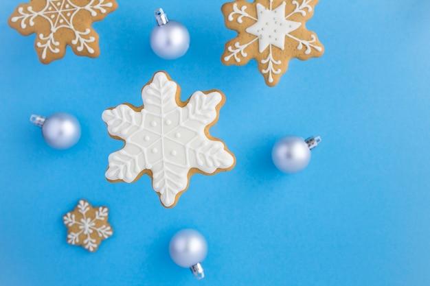 Bovenaanzicht van kerstkoekjes in de vorm van sneeuwvlokken op het blauwe oppervlak