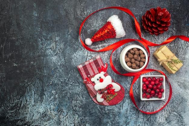 Bovenaanzicht van kerstman hoed en cornel chocolade nieuwjaar sok rode conifer kegel aan de linkerkant op donkere ondergrond