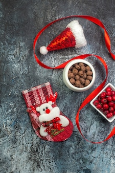 Bovenaanzicht van kerstman hoed en cornel chocolade nieuwjaar sok rode conifer kegel op donkere ondergrond
