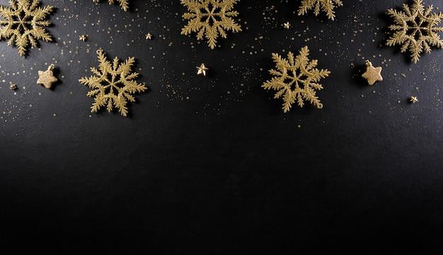 Bovenaanzicht van kerstmissneeuwvlok en sterren op zwarte houten achtergrond.