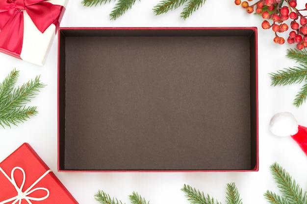 Bovenaanzicht van kerstsamenstelling, geschenkdoos, dennenappels, dennentakken en open de doos met ruimte om product te zetten