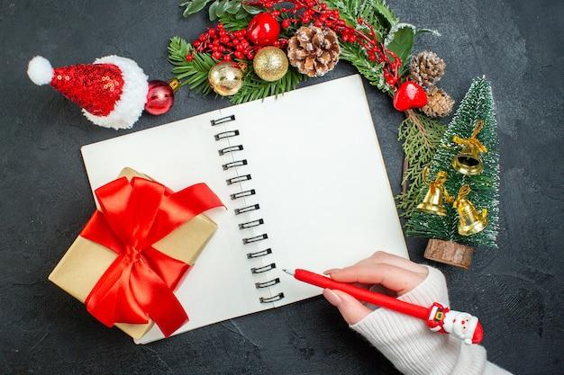 Bovenaanzicht van kerstsfeer met fir takken kerstman hoed hand met pen op laptop op donkere achtergrond