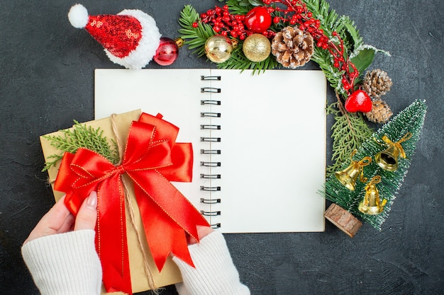 Bovenaanzicht van kerstsfeer met fir takken kerstman hoed xsmas boom rood lint op notebook op donkere achtergrond