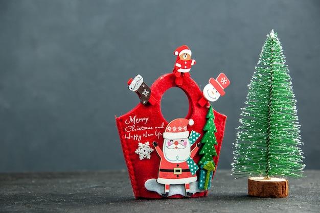 Bovenaanzicht van kerststemming met decoratieaccessoires op nieuwjaarsgeschenkdoos en kerstboom op donkere ondergrond
