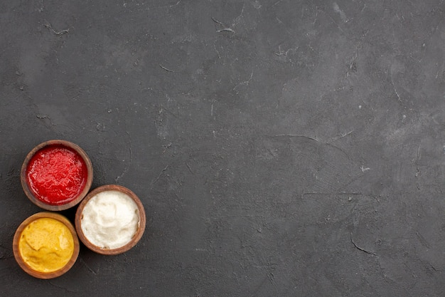 Bovenaanzicht van ketchup en mosterd met mayonaise in kleine potten op zwart