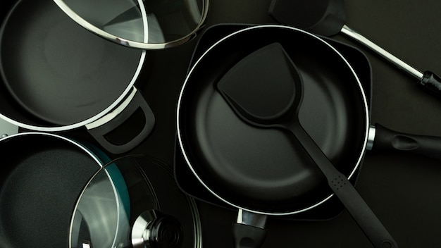 Bovenaanzicht van keuken gebruiksvoorwerp pan en pot op zwart leer achtergrond.