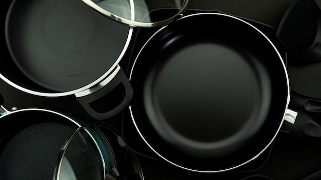 Bovenaanzicht van keuken gebruiksvoorwerp pan en pot op zwart leer.