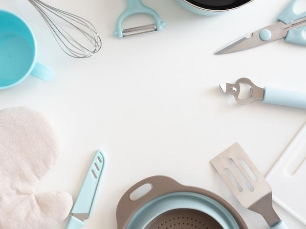 Bovenaanzicht van keuken kamer concept met keukengerei op witte tafel achtergrond.