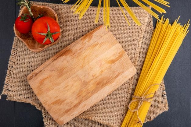 Bovenaanzicht van keukenbord met rauwe spaghetti en tomaten op een beige servet op een zwarte ondergrond
