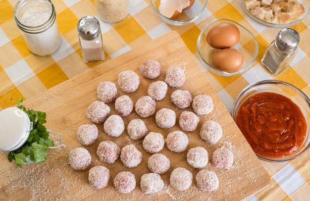 Bovenaanzicht van keukentafel met gehaktballen klaar voor pan, houten snijplank en rauwe ingrediënten