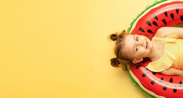 Bovenaanzicht van kind meisje in een zwembroek liggend op een opblaasbare zwemring op gele muur