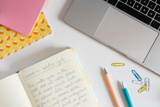 Bovenaanzicht van kinderbureau met laptop en notebook