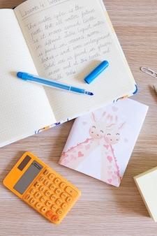 Bovenaanzicht van kinderbureau met notitieboekje en rekenmachine