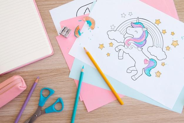Bovenaanzicht van kinderbureau met tekeningen en potloden