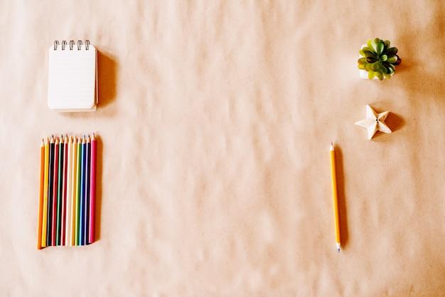 Bovenaanzicht van kinderen spelen opstelling met houten kleurpotloden en ongeverfd papier met bladeren aan de balie.