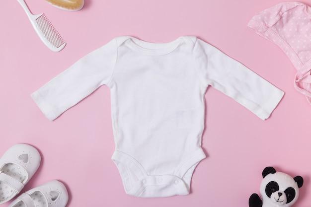 Bovenaanzicht van kinderkleding, wit babyrompermodel op een roze oppervlak