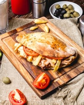 Bovenaanzicht van kip doner met tomaat frietjes en augurken