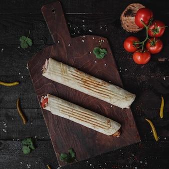 Bovenaanzicht van kip doner verpakt in lavash op een houten snijplank