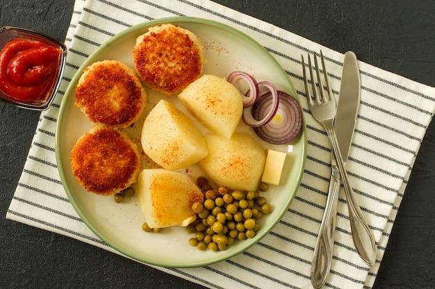 Bovenaanzicht van kip gepaneerde geroosterde schnitzels met gekookte aardappel en gekiemde groene erwt geserveerd met ui en ketchup.