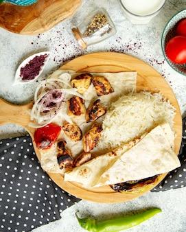 Bovenaanzicht van kip kebab geserveerd met rijst flatbread ui en sumak