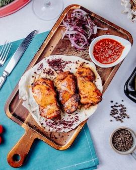 Bovenaanzicht van kip kebab met rode uien op een houten bord