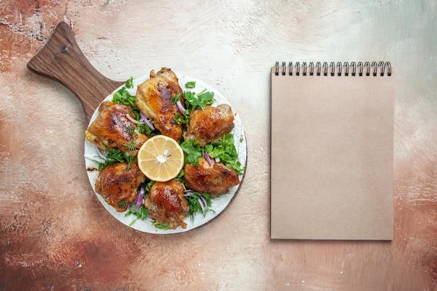 Bovenaanzicht van kip, kip, kruiden, ui, citroen, op het bord naast het room-notitieboekje